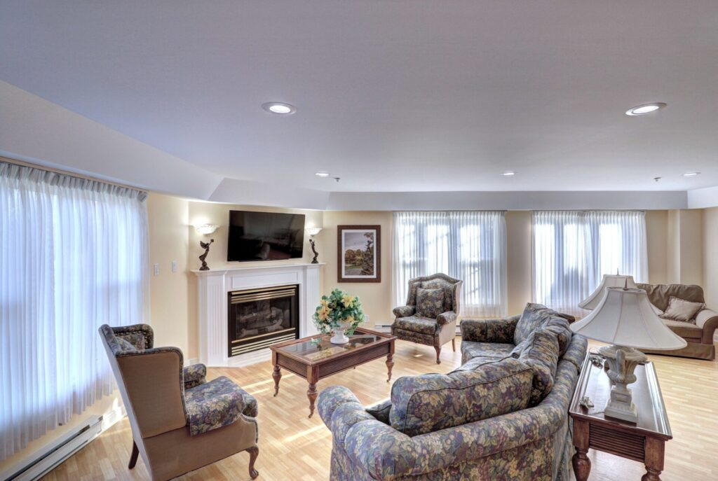 A comfortable assortment of seating in front of a fireplace and large mounted television.