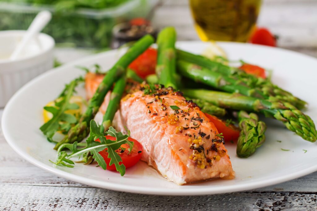 A table with a white lace table cloth and a white plate with salmon, asparagus, and greens