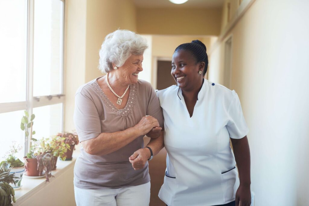 Patient and nurse walk down a bright hallway near a window ledge with potted plants on it.