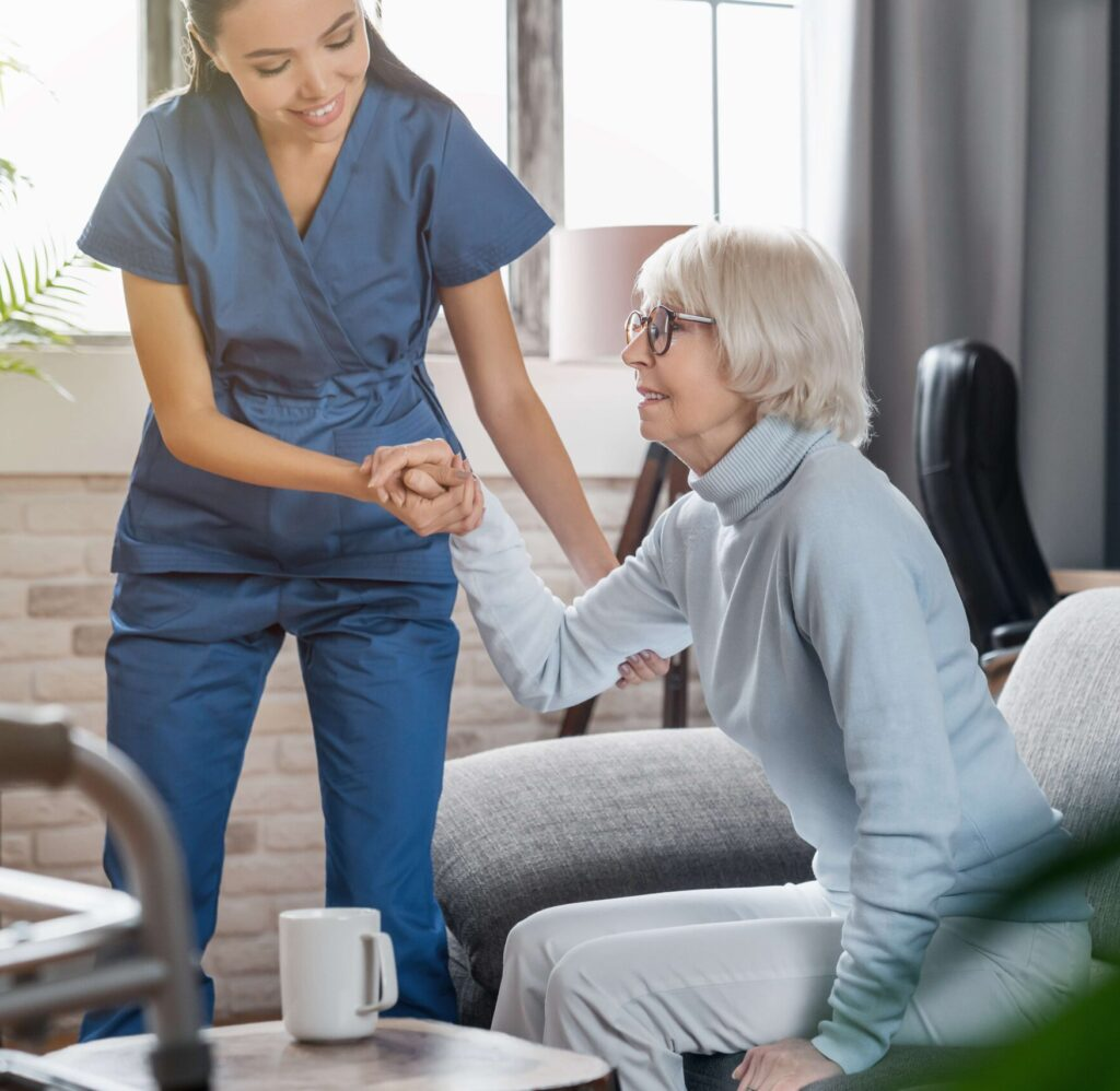 Nurse assisting a female resident stand up from a seated position on a sofa.