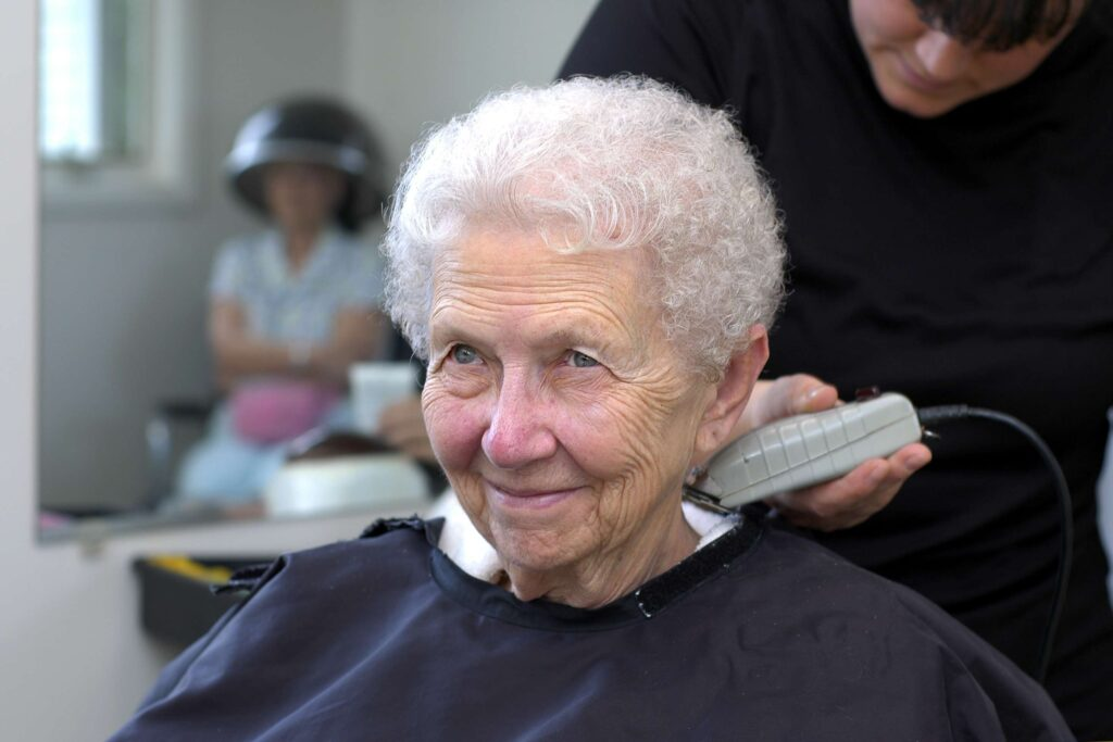 A woman sits in our on-site salon chair as a hairdresser trims her hair.