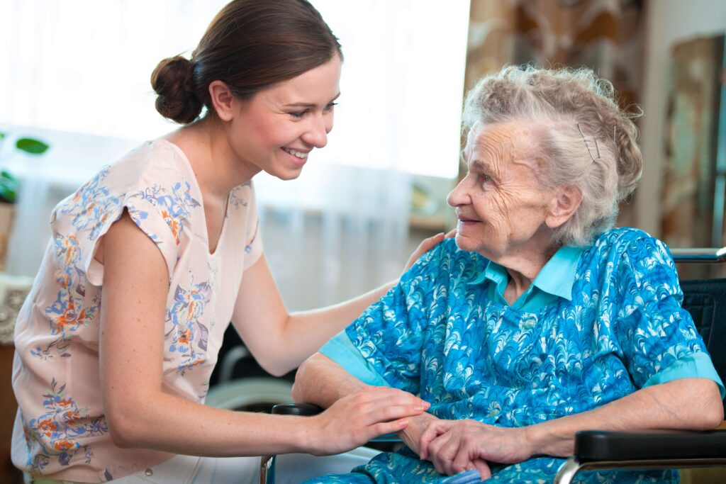 A Team member happily greets a resident who smiles back.